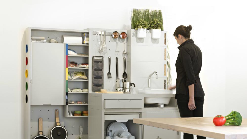 Visão geral da cozinha do futuro, com a mesa interativa em primeiro plano. No detalhe, a demonstradora utiliza a torneira que seleciona de forma inteligente a água.