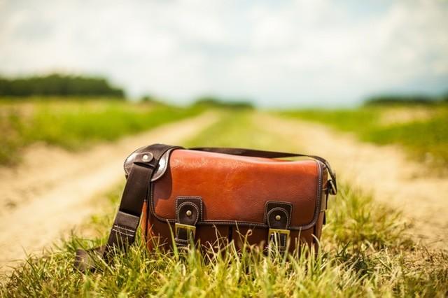 Imagem de uma bolsa marrom no meio de uma estrada de terra e mato