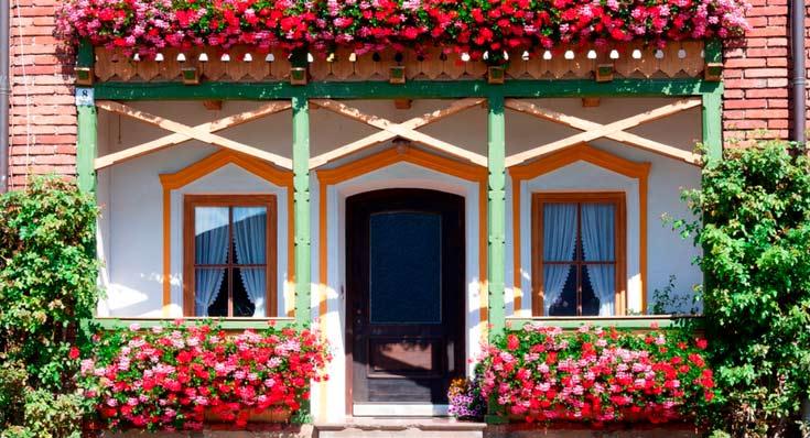 """Imagem de uma casa com a varanda com flores com a descrição """"Cobertura vendaval e tornado"""""""