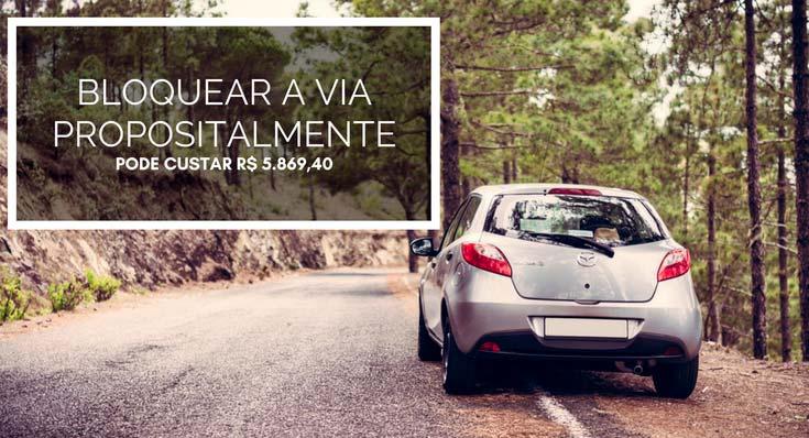 """Imagem de carro prata na estrada com a descrição """"Bloquear a via propositalmente pode custar R$ 5.869,40"""""""