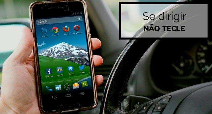 """Imagem de uma pessoa segurando o celular dentro do carro com a descrição """"Se dirigir, não tecle"""""""