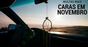 """imagem do interior do carro com vista para o por do sol e frase """"multas mais caras em novembro"""""""