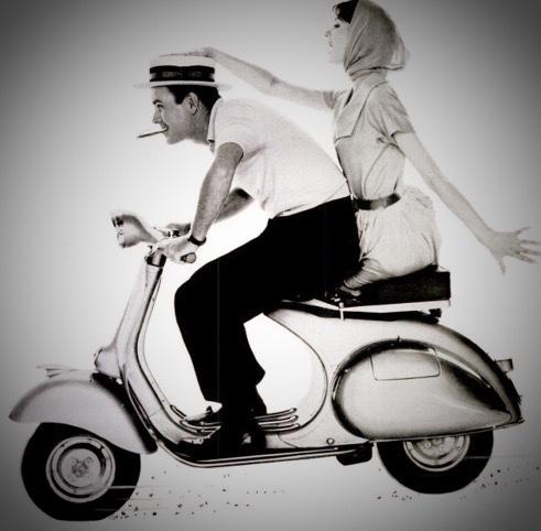 Casal em foto antiga andando de vespa