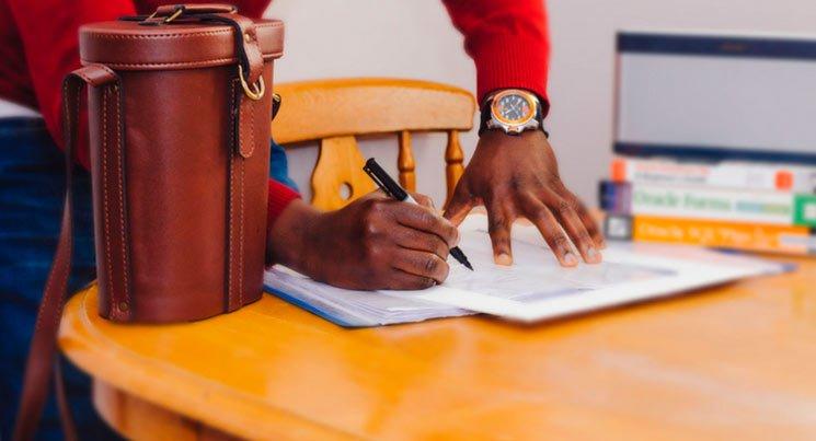 imagem de um homem assinando documentos