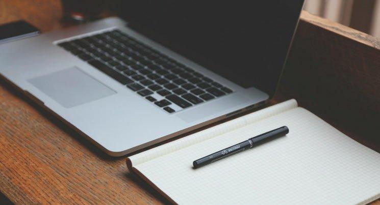 imagem de notebook e caderno, para mostrar a cobertura de escritório em residência.