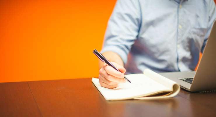 imagem de uma pessoa escrevendo em um caderno