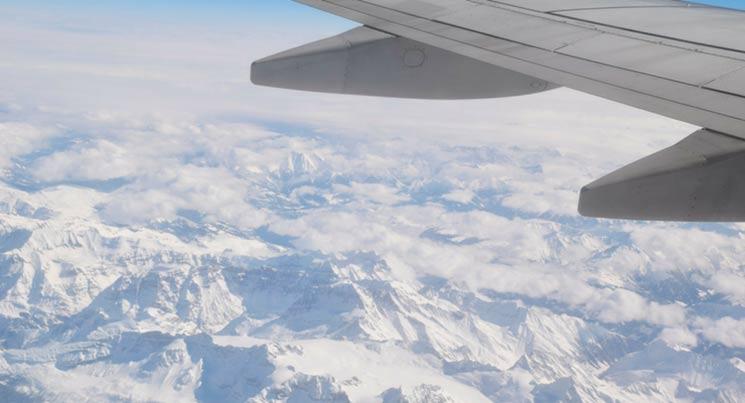 """imagem de uma asa de avião com montanhas em baixo com a legenda """"problemas em viagem"""""""