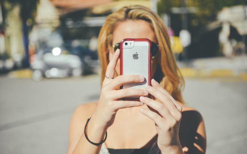 Mulher tirando foto com um iphone