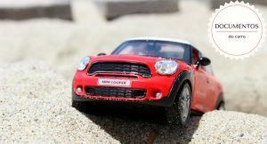 """Imagem de uma miniatura de um mini cooper na areia com a descrição """"documentos do carro"""""""