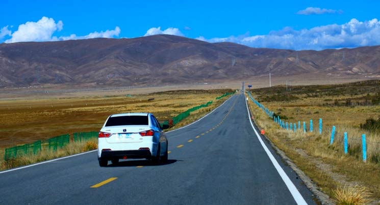 Imagem de um carro na estrada para ilustrar a postagem de revisões pré-pagas