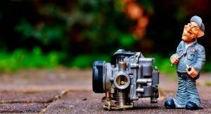 imagem de uma miniatura de mecânico com uma peça do motor, para ilustrar a postagem