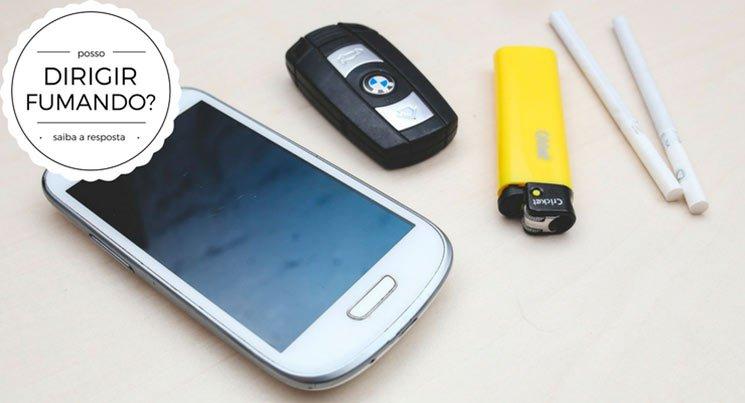 """Imagem de um celular, cigarro, isqueiro e controle do carro em cima de uma mesa com a legenda """"posso dirigir fumando? saiba a resposta"""""""