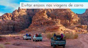 Imagem de uma estrada de terra no meio de montanhas de rochas e três carros com pessoas na capota, com a legenda: evitar enjoos nas viagens