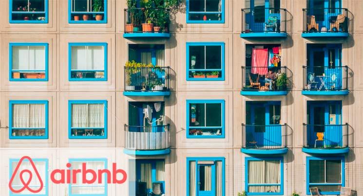 imagem de um prédio com varandas azuis com o logotipo do Airbnb Brasil