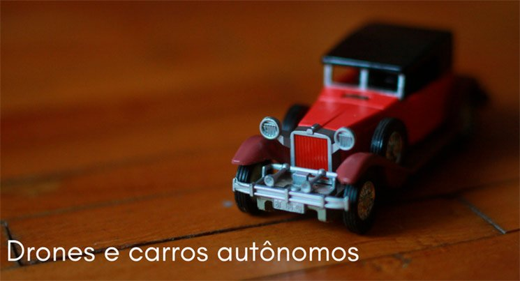 Imagem de uma miniatura de carro vermelho antigo em cima de uma mesa de madeira com a descrição: drones e carros autônomos