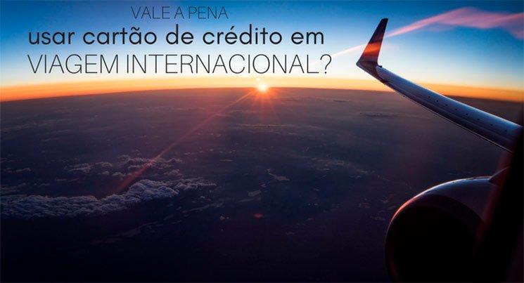Imagem de uma foto tirada dentro do avião, com o por do sol azulado e uma asa de avião. Texto na imagem: vale a pena usar cartão de crédito em viagem internacional
