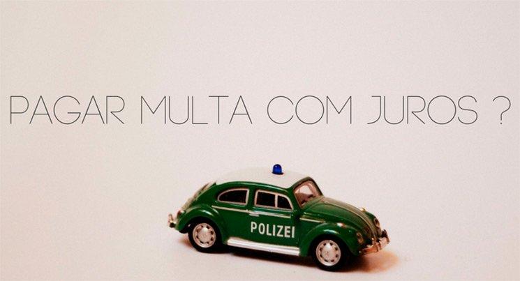 Imagem de uma miniatura de carro de policia em um fundo branco com a descrição: pagar multas com juros?