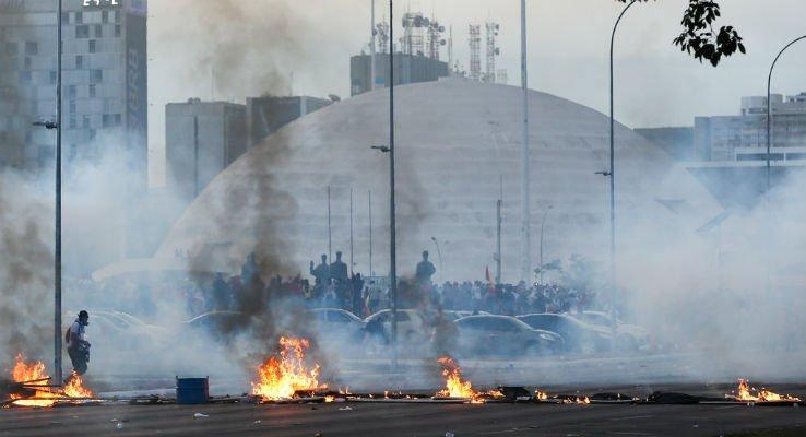 imagem de um protesto com carros pegando fogo