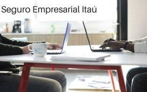 Imagem de dois homens na mesa com o computador com a descrição da imagem: Seguro empresarial Itaú