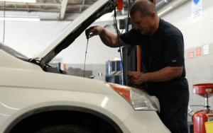 Imagem de mecânico medindo o óleo para post sobre carros com menor custo de manutenção