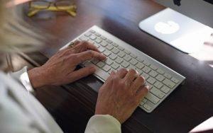 Imagem de pessoa teclando no computador para ilustrar guia sobre Plano de saúde no imposto de renda