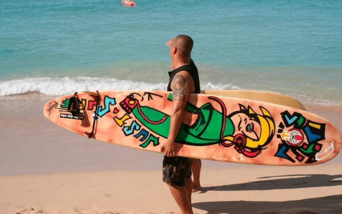 Imagem de surfista para ilustrar post sobre transportar bicicleta e prancha