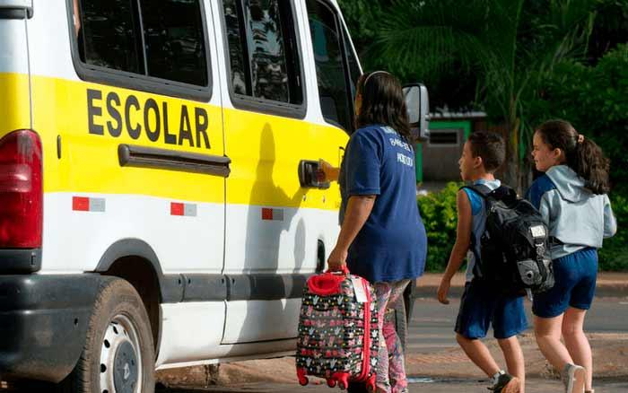 Imagem de crianças na van escolar para ilustrar post sobre volta às aulas