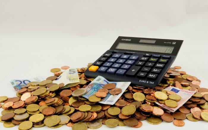 Imagem de calculadora e dinheiro ilustrando post sobre como organizar o orçamento familiar