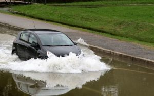 Imagem de veículo passando na enchente para ilustrar post sobre danos causados por água no motor