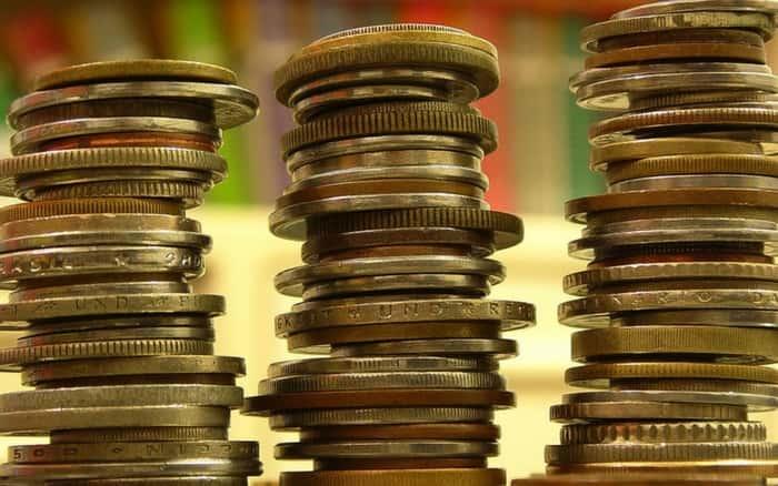 Imagem de moedas para ilustrar post sobre como economizar dinheiro ganhando pouco