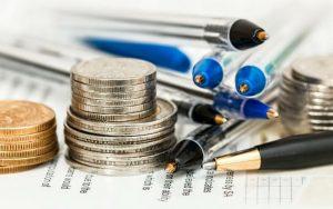 Imagem de caneta e moedas para ilustrar post sobre investimentos para iniciantes