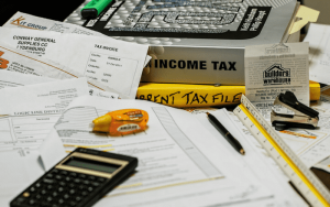 Imagem de papel, caneta e calculadora para ilustrar post sobre Como declarar aluguel recebido no imposto de renda