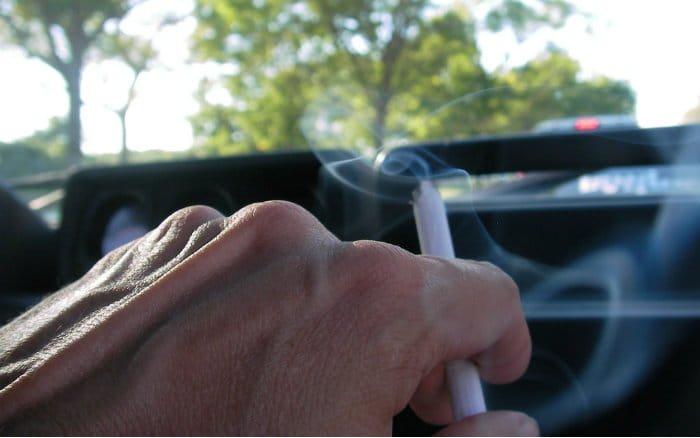 Pessoa fumando e dirigindo para post sobre multa por fumar dentro do carro