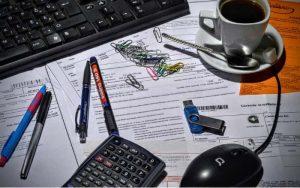 Imagem de computador, calculadora e papais para ilustrar guia sobre como declarar imposto de renda passo a passo