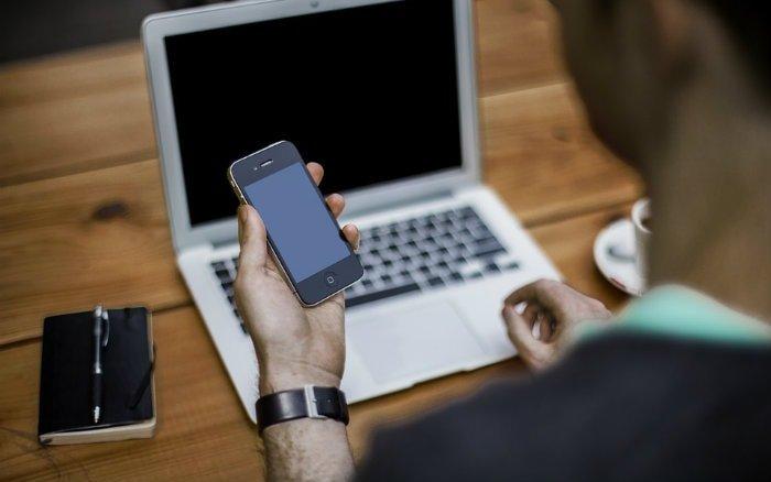 imagem de pessoa mexendo no computador e celular para ilustrar post sobre como saber o saldo do FGTS