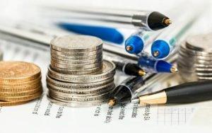 Imagem de moeda e canetas ilustrando post sobre o que é LCA