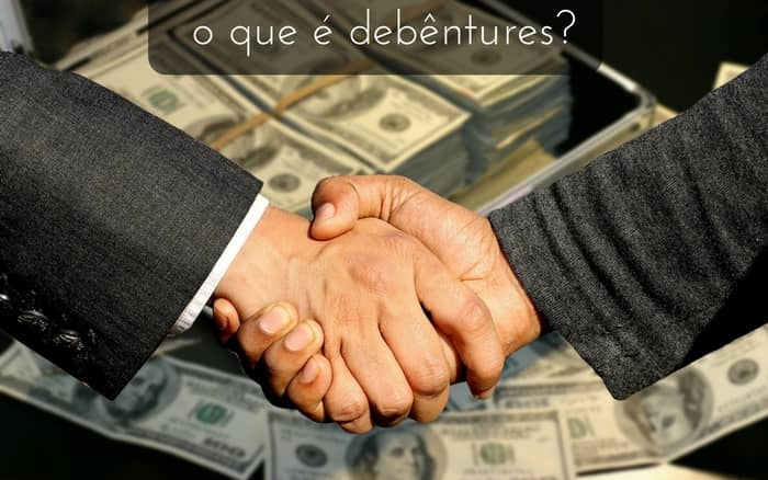imagem de aperto de mão de dois homens com dinheiro ao funco. legenda: o que é debêntures