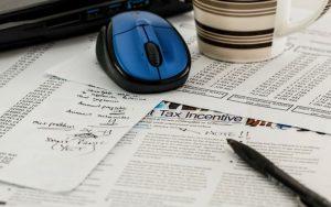 Imagem de papéis e caneta para ilustrar post sobre Como declarar LCA no imposto de renda