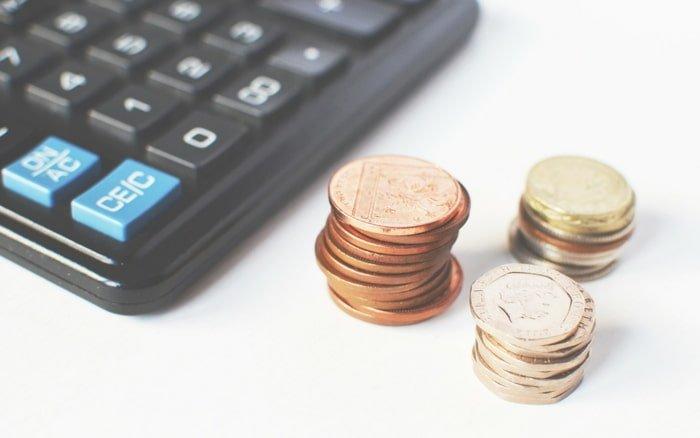 Imagem de moedas e calculadora para ilustrar post sobre Como investir na bolsa de valores com pouco dinheiro