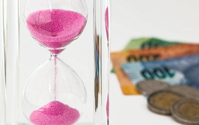 Imagem de ampulheta e dinheiro ilustrando guia sobre como funciona a previdência privada