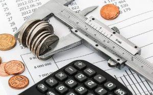 Imagem de moedas e calculadora para ilustrar post sobre Como declarar dependentes no imposto de renda