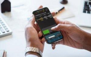 Imagem de celular com dados financeiros para ilustrar post sobre COE (Certificado de Operações Estruturadas)