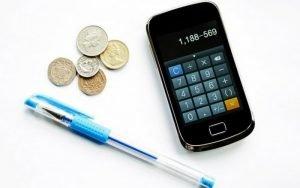 Imagem de celular, caneta e moedas para ilustrar post sober Quem deve declarar imposto de renda