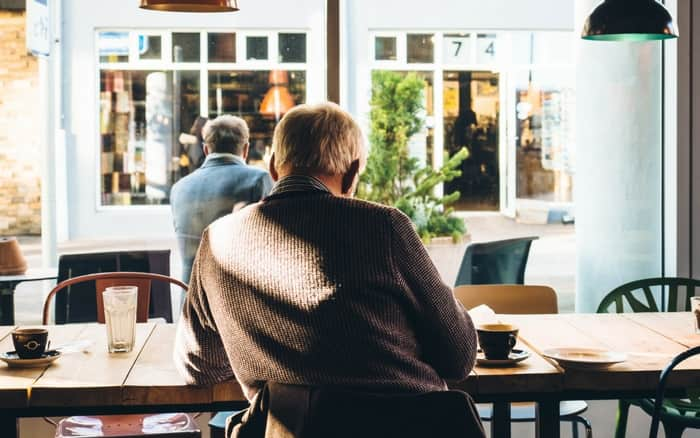 Imagem de senhor sentado de costas para ilustrar post sobre Aposentado paga imposto de renda