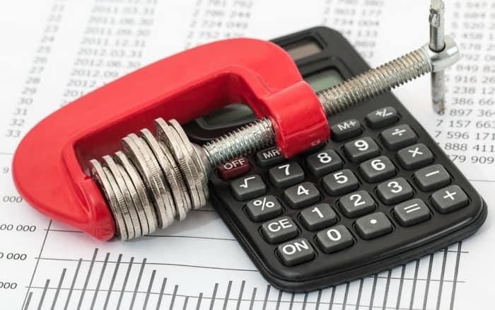 Imagem de calculadora e moedas para ilustrar post sobre Como declarar poupança no imposto de renda