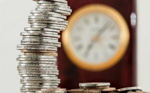 Imagem de moeda e relógio para ilustrar texto sobre carteira de investimentos