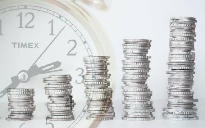 Imagem de moeda e relógio ilustrando texto sobre quem pode emitir debêntures