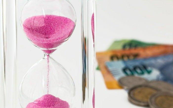 Imagem de dinheiro e ampulheta ilustrando texto sobre como investir no tesouro direto
