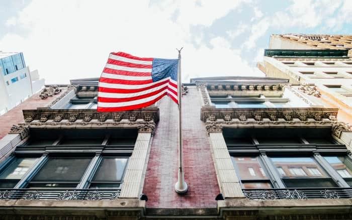 imagem de um prédio com uma bandeira americana para exemplificar a postagem sobre como morar nos EUA