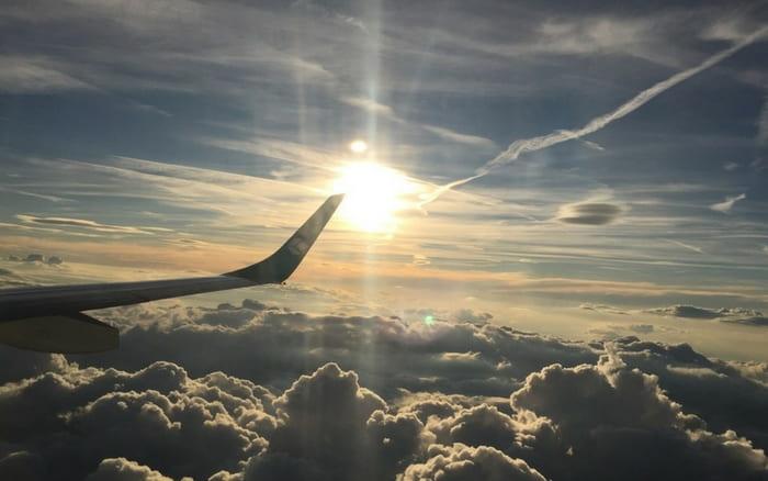 Imagem de avião entre as nuvens para ilustrar post sobre o que é booking
